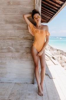 木製の壁にポーズをとるエレガントな水着のスリムな裸足の女の子。晴れた週末に海のリゾートで身も凍るような愛らしい白人女性。