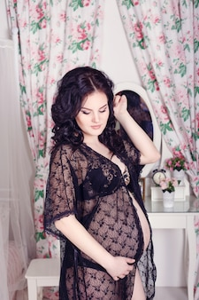 Slim beautiful pregnant woman sitting on the bed in the bedroom. beautiful lingerie. stylish and sexy pregnancy.