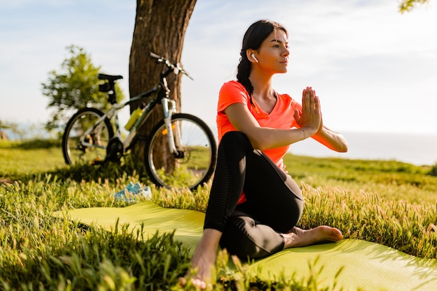 Slim beautiful woman doing sports in morning in park doing yoga