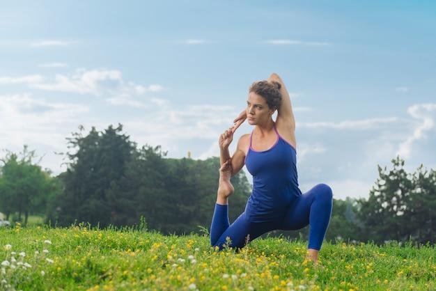 Стройная красивая женщина чувствует себя отдохнувшей и растянутой, сидя на зеленой траве