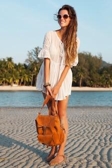革のバックパックを保持している日没の熱帯のビーチを歩く白い綿のドレスのスリムな美しい女性。