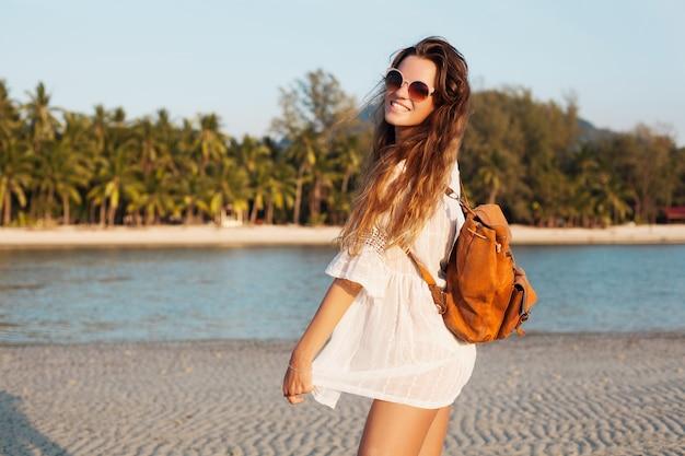 Худенькая красивая женщина в белом платье из хлопка, идущая на тропическом пляже на закате, держа кожаный рюкзак.