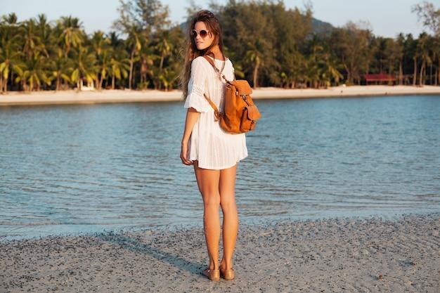 革のバックパックと日没の熱帯のビーチを歩く白い綿のドレスのスリムな美しい女性。