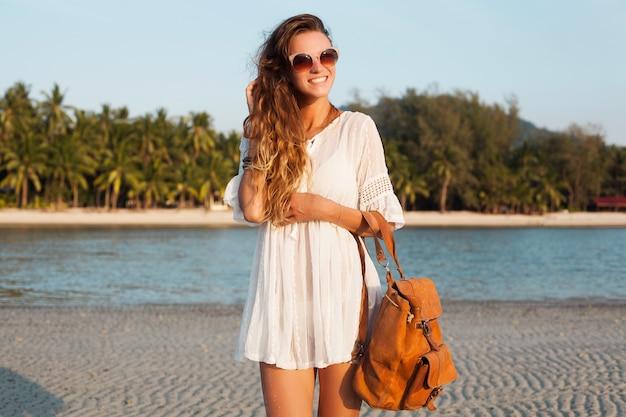 革のバックパックを保持している日没の熱帯のビーチで白いドレスのスリムな美しい女性。