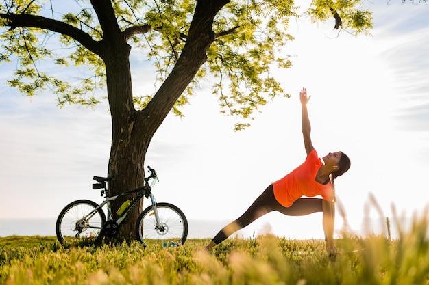 Стройный силуэт красивой женщины занимается спортом утром в парке, занимаясь йогой