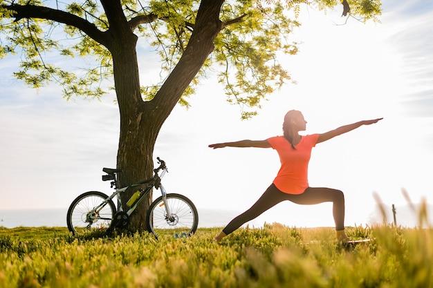 Siluetta sottile della bella donna che fa sport nella mattina nel parco che fa yoga