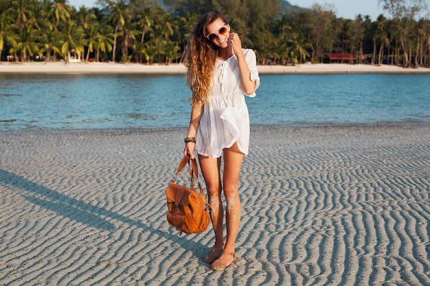Slim beautiful woman in white cotton dress walking on tropical beach on sunset holding leather backpack.