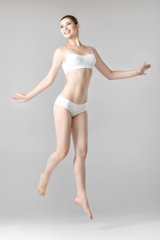 회색에 흰색 란제리 점프에 완벽한 몸매를 가진 슬림 아름다운 여인