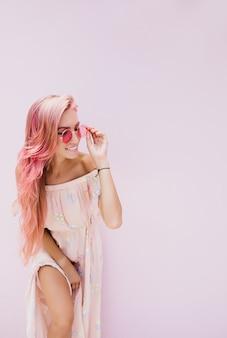부드럽게 미소로 긴 분홍색 머리를 가진 슬림 아름다운 여자.