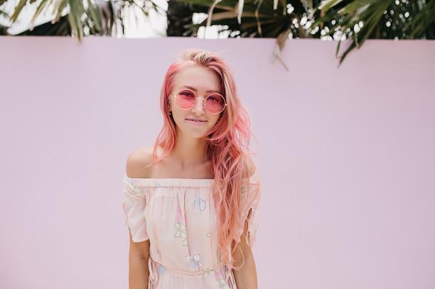 優しい笑顔で長いピンクの髪を持つスリムな美しい女性。