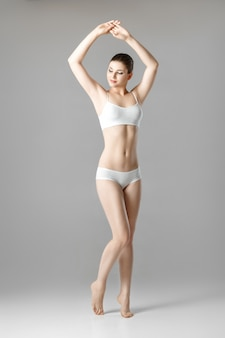 Slim beautiful woman with a perfect body in white lingerie on a gray