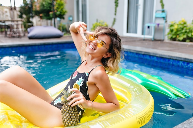 Slim blissful girl holding pineapple while posing at summer resort. outdoor portrait of happy caucasian lady chilling in pool with exotic fruits.