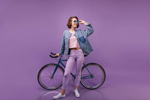 Стройная жизнерадостная женщина позирует с велосипедом. кудрявая женская модель в фиолетовых штанах в помещении в полный рост.