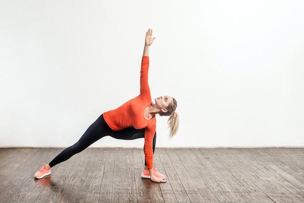 ヨガを練習し、トリコナサナの三角形のポーズで立って、柔軟性のために筋肉を訓練するタイトなスポーツウェアのスリムなブロンドの女性。自宅でのヘルスケア、スポーツ活動、トレーニング。屋内スタジオショット
