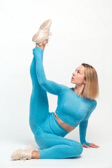 날씬한 금발 여성이 요가를 연습하고 요가 포즈를 취하고 유연성을 위해 근육을 훈련합니다. 건강 관리, 스포츠 활동 및 운동 개념