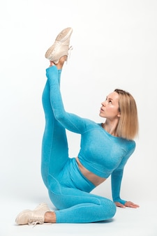 Slim blond woman in tight sportswear practicing yoga, standing in yoga pose, training muscles for flexibility. health care, sports activity and workout concept