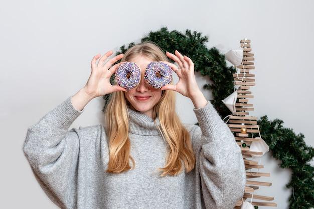 彼女の目にカラフルなドーナツを保持しているスリムなブロンドの女性、お菓子を楽しんでいる長い髪の魅力的な若い女性