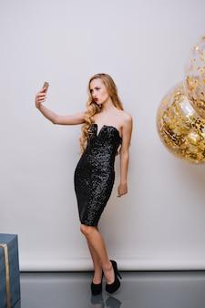 Стройная блондинка в модном черном платье делает селфи возле гелиевого шара на дне рождения. крытый портрет в полный рост молодой женщины с вьющейся прической, позирующей во время празднования нового года.