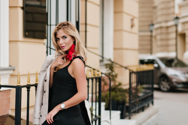 Стройная блондинка в модных наручных часах стоит возле железного забора с нежной улыбкой и позирует утром