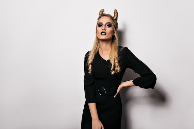 Slim blonde woman in witch costume posing with serious face expression. indoor shot of stunning female model preparing for halloween.