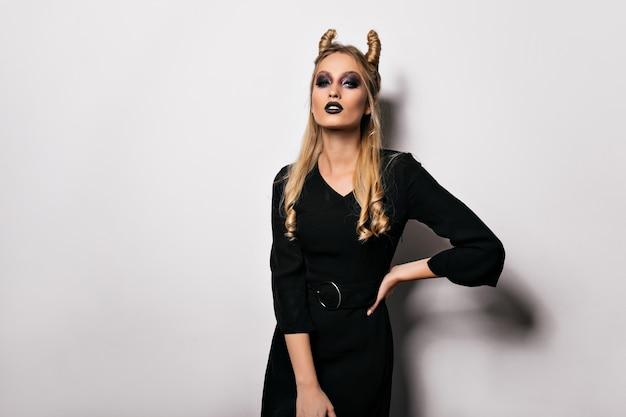 Slim donna bionda in costume da strega in posa con l'espressione del viso serio. tiro al coperto di un modello femminile sbalorditivo che si prepara per halloween.