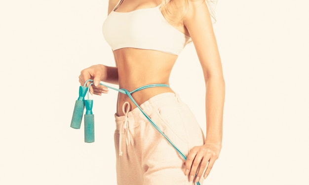 Slim body, jump rope. girl with perfect waist with a jump rope in hands. fit fitness girl measuring her waistline with measure tape.
