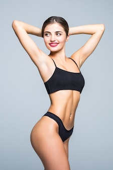 Slim body of young woman in black bikini. girl with healthy sporty figure on white wall