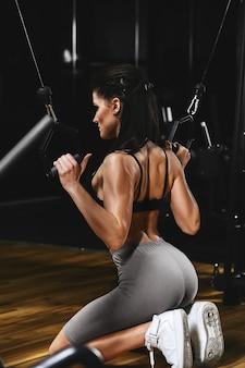 날씬한 보디 빌더 소녀가 체육관에서 팔 운동을합니다. 스포츠 컨셉, 지방 연소 및 건강한 라이프 스타일.