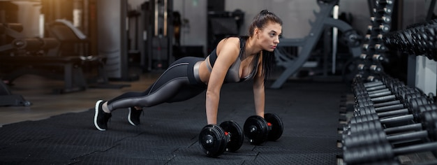 Slim, bodybuilder girl, lifts heavy dumbbell standing in front of the mirror while training in the gym. sports concept, fat burning and a healthy lifestyle. high quality photo