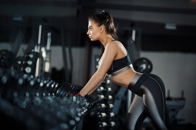 Slim, bodybuilder girl, lifts heavy dumbbell standing in front of the mirror while training in the gym. sports concept, fat burning and a healthy lifestyle