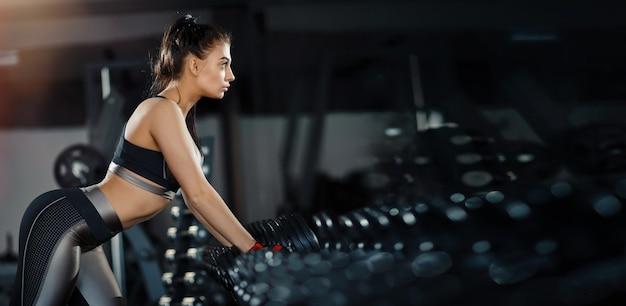 スリムなボディービルダーの女の子は、ジムでトレーニングしている間、鏡の前に立っている重いダンベルを持ち上げます。スポーツのコンセプト、脂肪燃焼、健康的なライフスタイル。