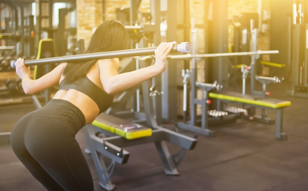 체육관에서 그녀의 시체를 기울이기 그녀의 어깨에 바디 바 체조 운동을하는 슬림 갈색 머리 선수. 뒷면보기