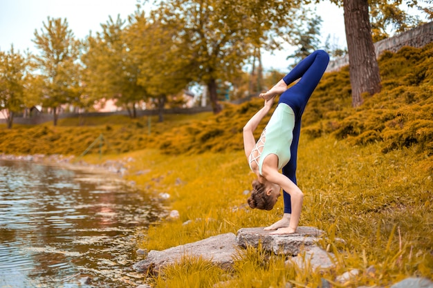 Slim brunette girl goes in for sports and performs yoga poses in the fall in nature by the lake