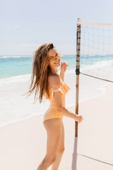 Slim brunette girl playfully looking over shoulder while posing on sea coast. outdoor photo of charming young lady wears orange swimsuit smiling beside volleyball set.