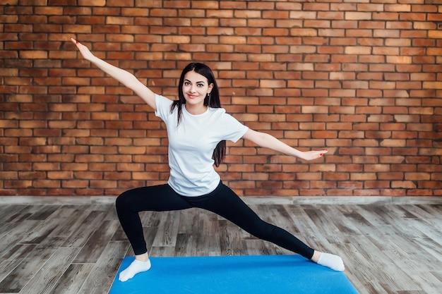La donna castana esile pratica l'yoga in studio retroilluminato bianco.
