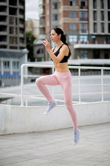 Slim brunette woman wears sports clothes jumping during her fitness workout