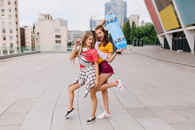 Ragazze spensierate esili che ballano divertenti sulla piazza godendo il fine settimana estivo e il bel tempo