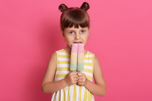 Slim caucasian girl kid holds two big ice cream looks with her happy eyes, having funny knots, posing isolated over pink wall, female kid biting tasty ice cream.