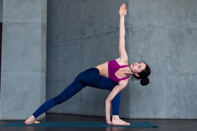 Slim caucasian girl standing in side angle pose, parsvakonasana, during her yoga routine in gym