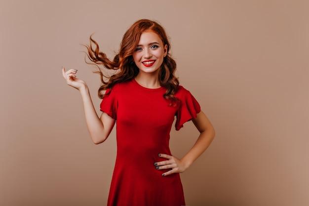 Стройная кавказская женщина в красном платье смеется. великолепная рыжая девушка играет с волосами во время фотосессии.