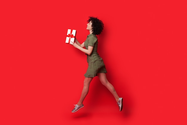 Slim caucasian woman with curly hair running on a red studio wall with a present giving it to somebody