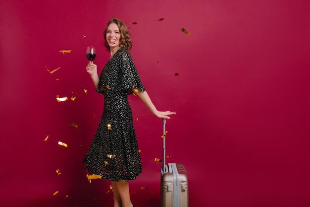 Стройная жизнерадостная дама с радостным выражением лица пьет вино и держит чемодан