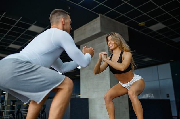 체육관에서 큐브에서 균형 운동을 하는 슬림 커플. 스포츠 클럽의 남녀, 활동적인 건강한 생활 방식
