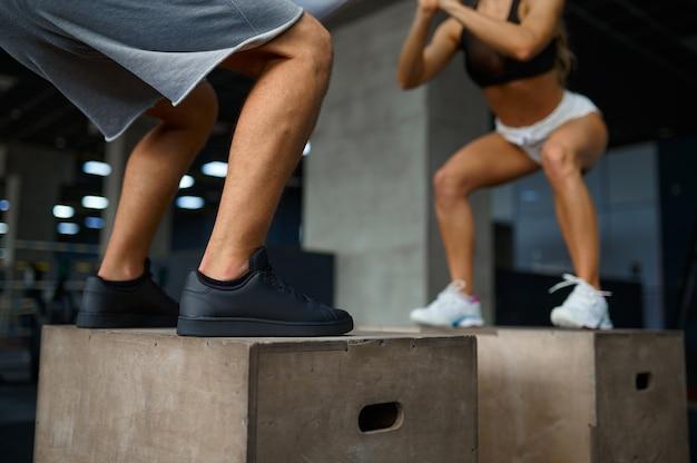 체육관에서 큐브에서 균형 운동을 하는 슬림 커플