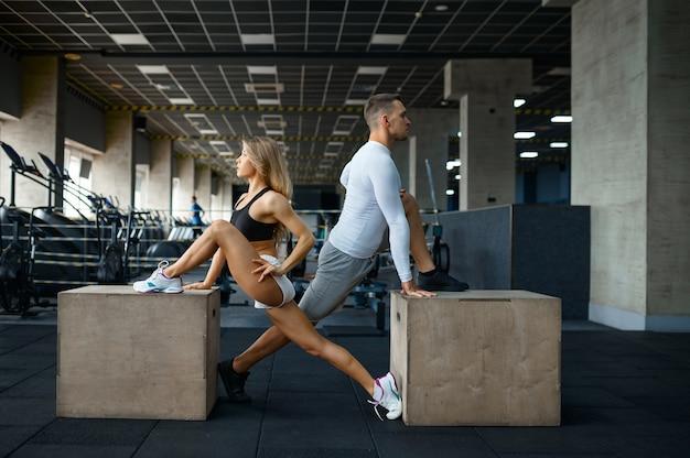 체육관에서 큐브에서 운동을 하는 슬림 커플