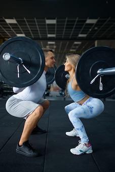 바벨을 가지고 운동을 하고 체육관에서 훈련하는 날씬한 커플. 스포츠 클럽에서 운동하는 운동 남자와 여자, 활동적인 건강한 생활 방식, 신체 건강