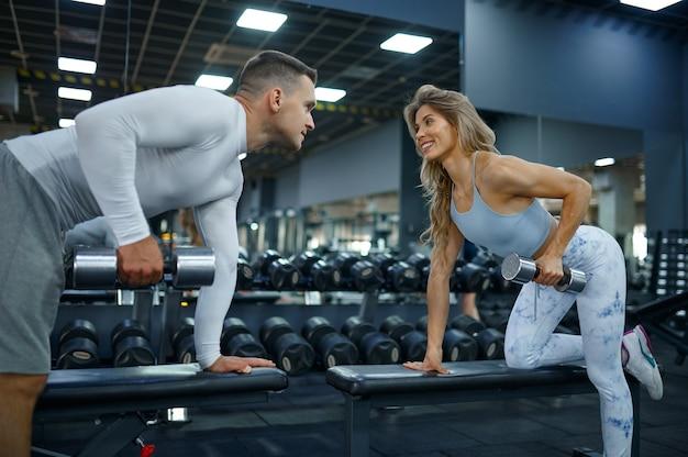 체육관에서 아령으로 운동을 하는 날씬한 커플