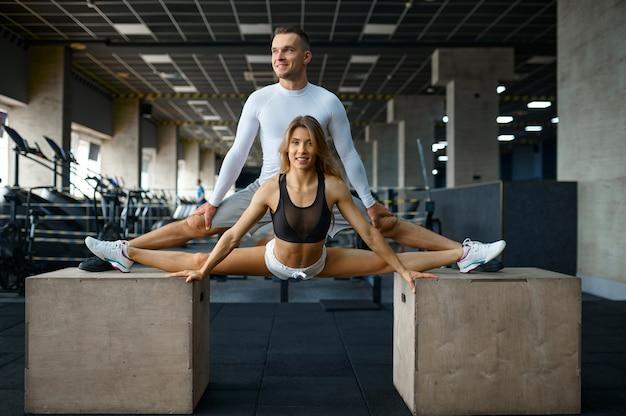체육관에서 큐브에서 스트레칭 운동을 하는 슬림 커플