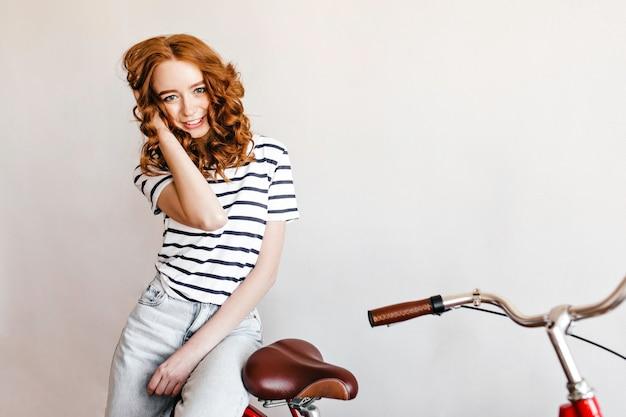 자전거와 함께 포즈를 취하는 청바지에 슬림 귀여운 아가씨. 자전거 근처에 서서 긍정적 인 감정을 표현하는 기쁜 곱슬 여자의 실내 사진.