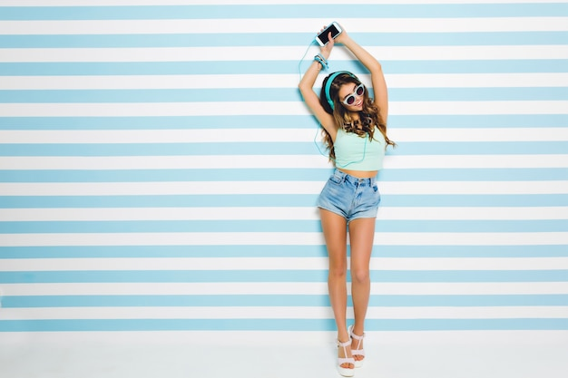 Slim cute young lady chilling at home, listening favorite song and dancing with happy smile. portrait of gorgeous girl in sunglasses with long tanned legs having fun on striped wall.